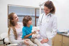 Dentista pediatrico che sorride al ragazzino con sua madre Immagine Stock