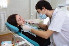 Dentista profissional que faz o controle dos dentes na cirurgia dental paciente fêmea Conceito de saudável Fotografia de Stock