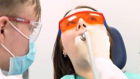 Dentista profissional que trabalha com o paciente na clínica moderna, conceito da medicina media Paciente novo em vidros protetor imagens de stock royalty free