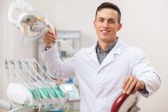 Dentista profissional que trabalha em sua clínica dental foto de stock royalty free