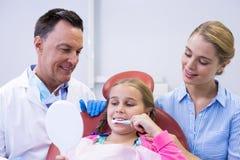 Dentista que ajuda ao paciente novo ao escovar os dentes imagens de stock royalty free