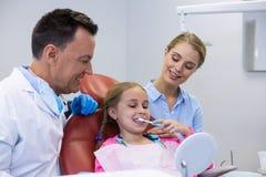 Dentista que ajuda ao paciente novo ao escovar os dentes fotos de stock