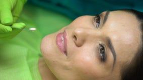 Dentista que compara el color del sellante que llena de los dientes naturales pacientes, primer almacen de video