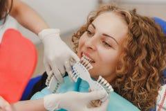 Dentista que compara la sombra paciente de los dientes del ` s con las muestras para el tratamiento del blanqueo imagen de archivo libre de regalías