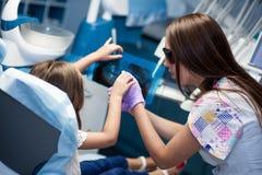 Dentista que cura um paciente da criança no escritório dental fotos de stock royalty free