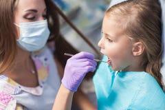 Dentista que cura um paciente da criança no escritório dental imagem de stock royalty free