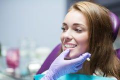 Dentista que cura a un paciente de la mujer Foto de archivo