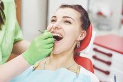 Dentista que cura a un paciente femenino en la estomatología Concepto de la prevención temprana y de la higiene oral imágenes de archivo libres de regalías