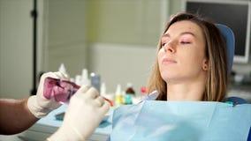 Dentista que dá óculos de proteção alaranjados protetores pacientes fêmeas vídeos de arquivo