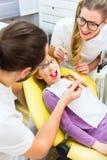 Dentista que da el tratamiento de la muchacha en cirugía dental Imágenes de archivo libres de regalías