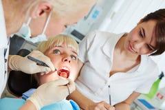 Dentista que da el tratamiento dental con la punta de prueba y el espejo Imagenes de archivo
