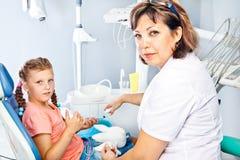 Dentista que da instrucciones de la higiene oral Imagenes de archivo