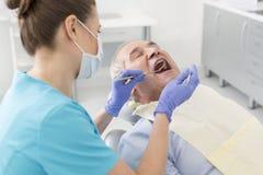 Dentista que examina la boca paciente mayor con el espejo anguloso y el escalador durante el tratamiento imagen de archivo libre de regalías