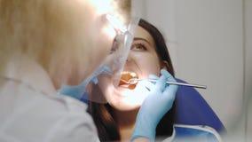 Dentista que examina los dientes de un paciente en la oficina del dentista metrajes