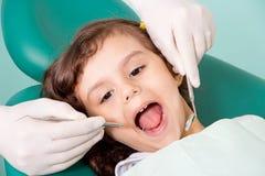 Dentista que examina poco girl& x27; dientes de s fotografía de archivo libre de regalías