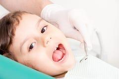 Dentista que examina poco girl& x27; dientes de s fotos de archivo