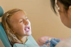 Dentista que examina poco girl& x27; dientes de s en clínica Niña que se sienta en una silla cerca de un dentista después del tra imágenes de archivo libres de regalías