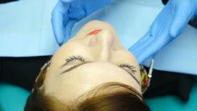 Dentista que examina por la junta del mandíbula del tacto Tiro ascendente cercano de la mujer joven en silla dental Doctor irrec almacen de video