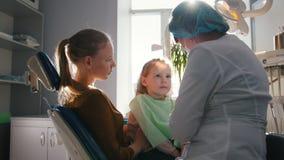 Dentista que examina a una niña que se sienta en su revestimiento del ` s de la mamá almacen de video