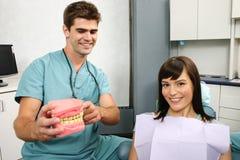 Dentista que explica al paciente Imagen de archivo