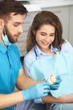 Dentista que explica ao paciente fêmea como escovar seus dentes imagem de stock