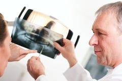 Dentista que explica la radiografía al paciente Fotografía de archivo