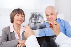 Dentista que explica o raio X aos pares superiores Fotos de Stock