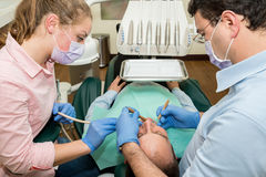 Dentista que faz um tratamento dental em um paciente Imagem de Stock Royalty Free