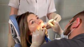 Dentista que fornece os dentes que limpam para um paciente da mulher filme