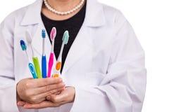 Dentista que guarda escovas de dentes com o DES diferente da cabeça e da cerda foto de stock