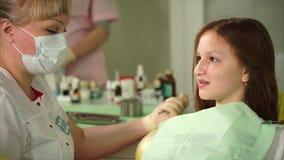 Dentista que habla con el paciente joven Chica joven que asiste al dentista almacen de metraje de vídeo