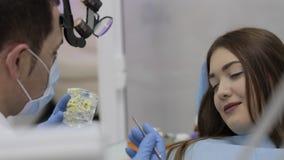 Dentista que habla con el paciente y que muestra un modelo de dientes metrajes