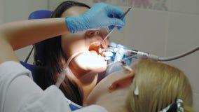 Dentista que hace un tratamiento dental en un paciente femenino almacen de metraje de vídeo