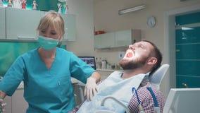 Dentista que hace una inyección del anestésico en las gomas y que habla con el paciente almacen de video