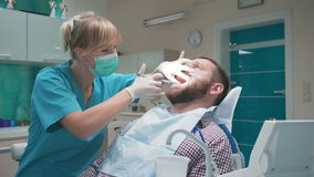 Dentista que hace una inyección del anestésico en las gomas y que mira a la cámara almacen de metraje de vídeo
