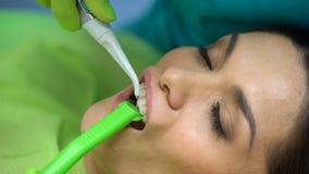 Dentista que lava el gel azul hacia fuera del diente, odontología cosmética, ayuda profesional almacen de metraje de vídeo