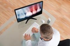 Dentista que mira la radiografía en el ordenador fotos de archivo