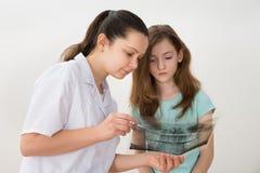 Dentista que mostra o raio X ao paciente fotografia de stock