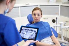 Dentista que mostra o raio X no PC da tabuleta à menina paciente imagem de stock