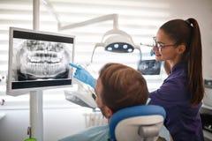 Dentista que muestra la cantidad de la radiografía de dientes al paciente fotos de archivo