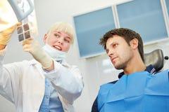 Dentista que muestra la carie paciente en imagen de la radiografía Imagen de archivo libre de regalías