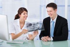 Dentista que muestra la radiografía del mandíbula al hombre de negocios en clínica Foto de archivo libre de regalías