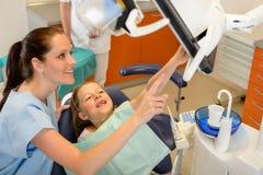 Dentista que muestra a niño procedimiento dental en monitor Imagen de archivo libre de regalías