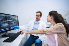 Dentista que muestra una radiografía de dientes al paciente femenino Fotos de archivo libres de regalías