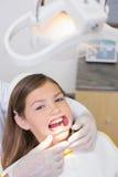 Dentista que pone el retractor de la boca en niña Fotografía de archivo