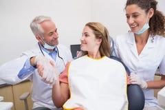 Dentista que sacude las manos con su paciente en la silla al lado del ayudante Fotos de archivo libres de regalías