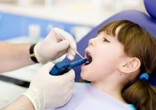 Dentista que usa a arma de enchimento dental na criança Imagens de Stock Royalty Free