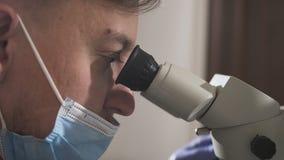 Dentista que usa el microscopio dental en la oficina dental moderna para la operación de un paciente de la mujer - odontología De metrajes