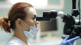 Dentista que usa el microscopio dental en odontología metrajes