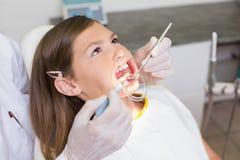 Dentista que usa el retractor de la boca en niña Foto de archivo